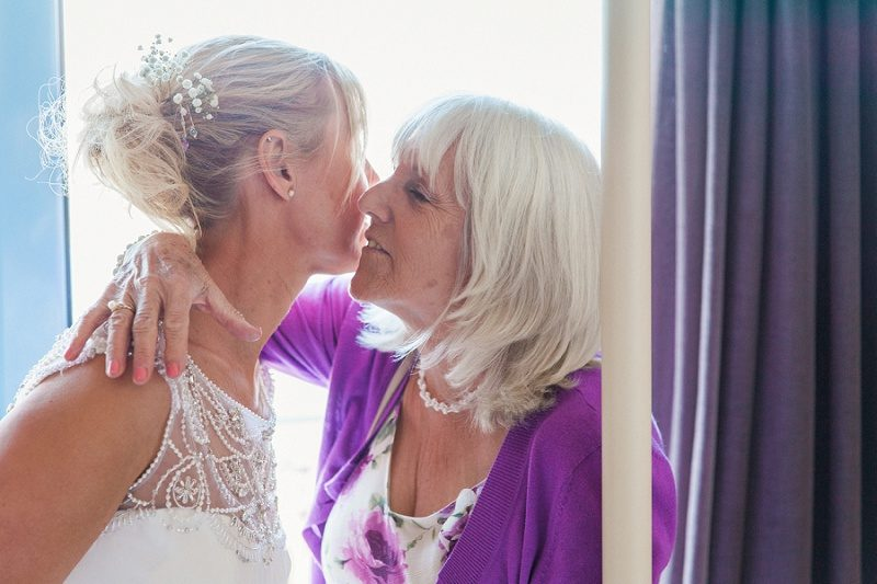 Mother and Bride Sharing a Moment Before Her Pastel Beach Wedding