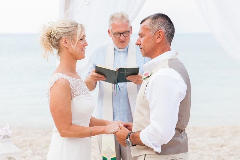 Bride and Groom Exchanging Vows During Their Pastel Beach Wedding