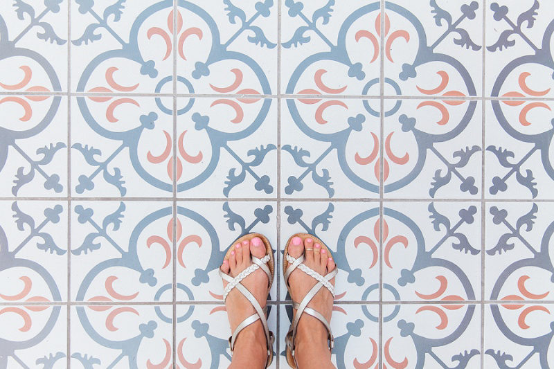 Feet in Sandals Against Blue White and Terracotta Tiles in Oia Santorini