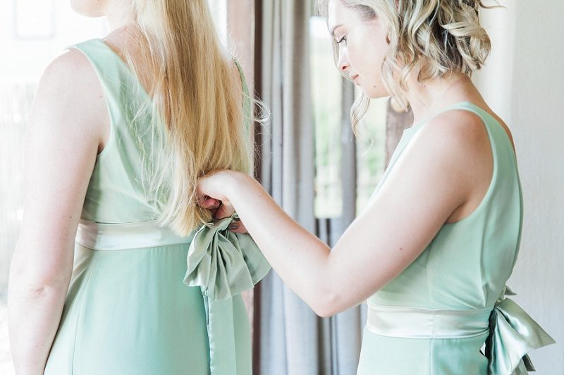 Bridesmaids Putting On Pistachio Dresses