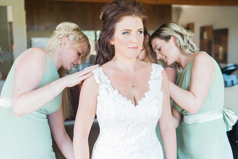 Bridesmaids Helping Bride Dress for Her Pistachio and White Wedding