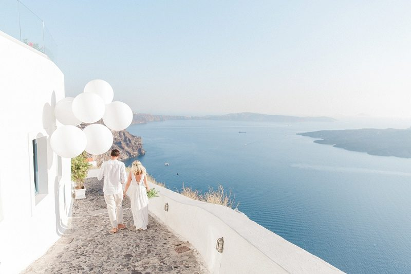 Newlyweds Walking Through Fira with Giant White Balloons