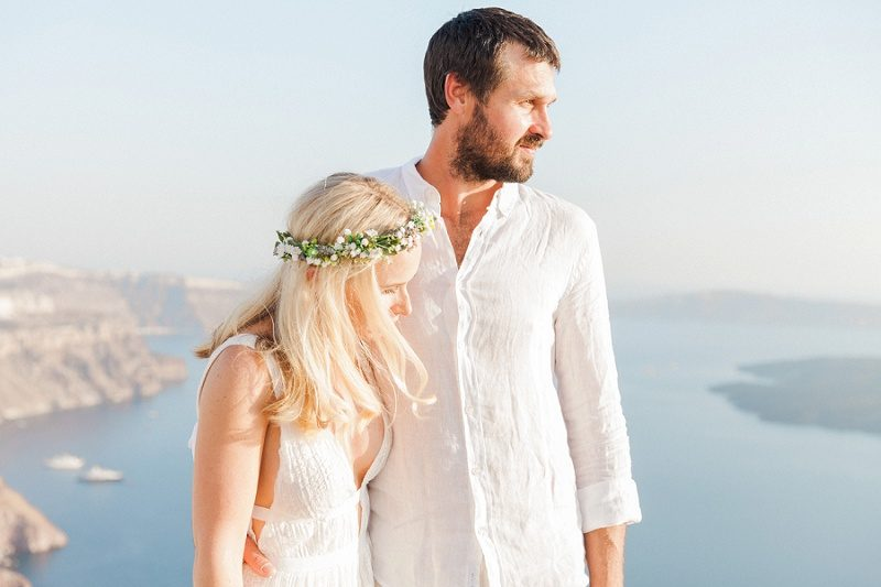 Couple Standing Together With a Backdrop of the Santorini Caldera
