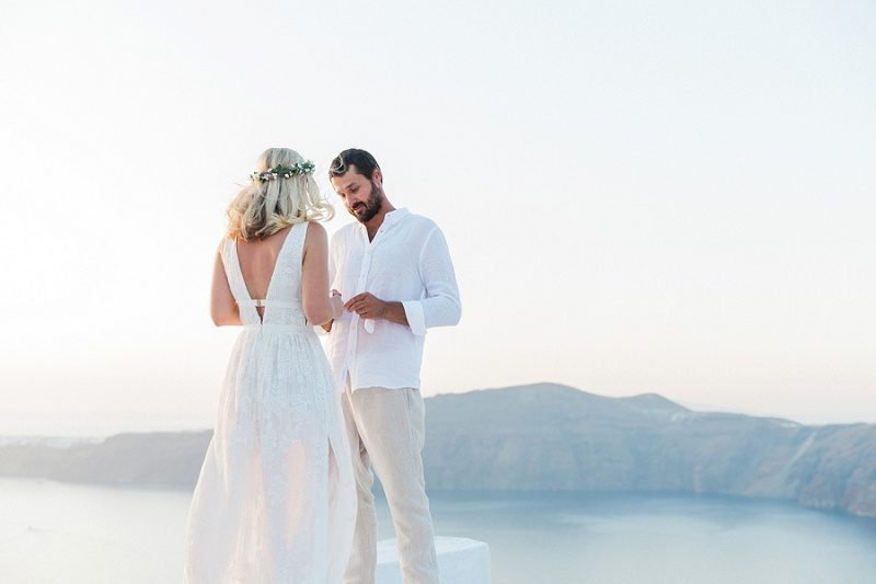Couple Exchanging Vows During Their Sunset Elopement In Santorini