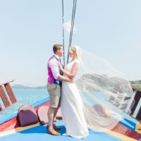 Bride wearing Laverne wedding dress by Catherine Deane and groom on a boat in Nidri   Maxeen Kim Photography