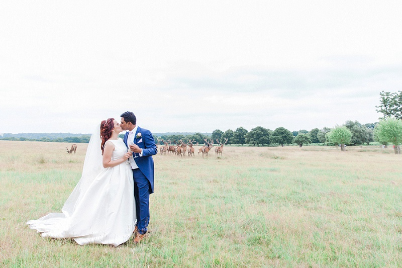 Bride and Groom Kissing in Richmond Park with Deer Behind Them