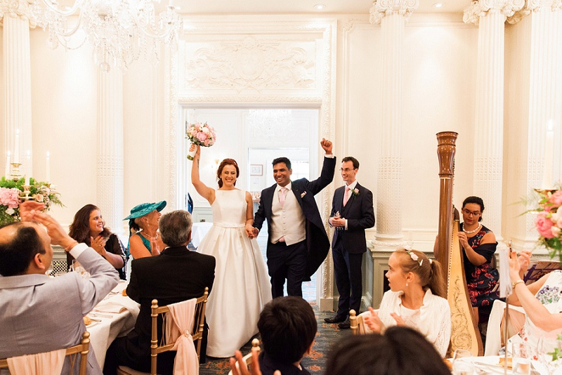 Bride and Groom with arms raised as they enter the reception of their Wedding at Warren House