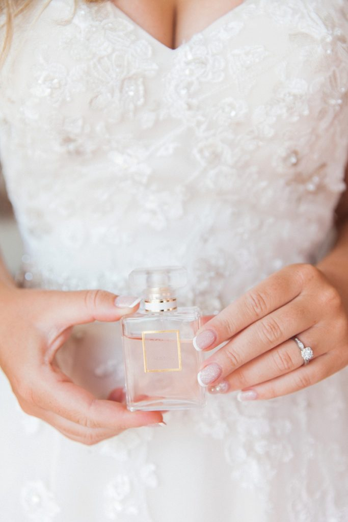 Close up image of the bride holding soft pink perfume bottle against her dress