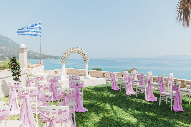 The Villa Rosa ceremony area with Greek flag, floral arch and decorated white chairs.
