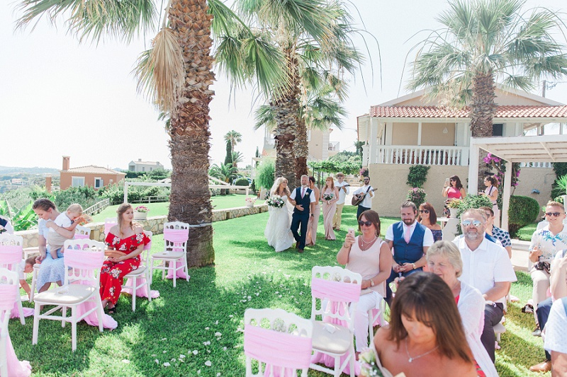 Bridal party entering the ceremony area at Villa Rosa on Kefalonia.