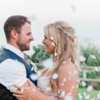 Bride and groom embracing under a shower of confetti on Kefalonia