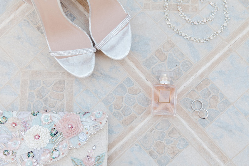 Brides details including heels, perfume and jewellery, laid out on the gorgeous pastel tiles